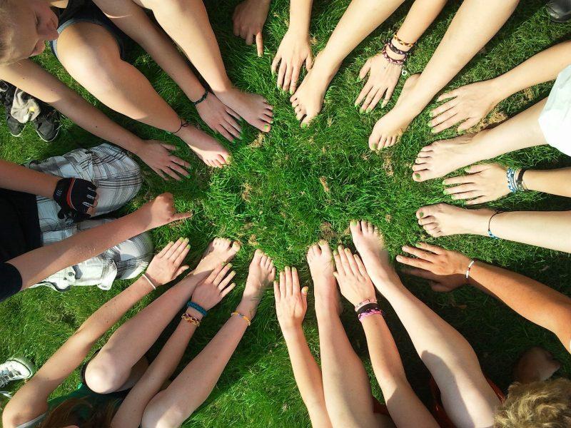 Die Hände und Füße von vielen Personen bilden einen Kreis